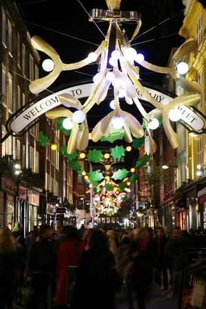 London, UK - November 17, 2011: Christmas Lights Display on Carnaby Street in London. The modern colourful Christmas lights attract and encourage people to shopping.