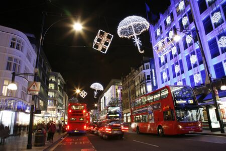 London, UK - November 18, 2011: Christmas Lights Display on Oxford Street in London. The modern colourful Christmas lights attract and encourage people to the street.