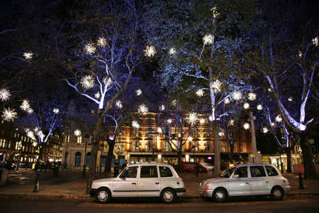 London, UK - November 30, 2011: Christmas Lights Display on Sloane Square in Chelsea, London. The modern colourful Christmas lights attract and encourage people to the street.