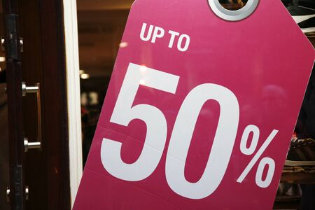Sale signs in shop window, big reductions photo