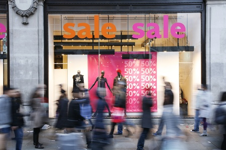 consumerism: Sale signs in shop window, big reductions
