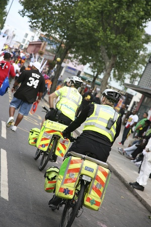 London, UK - August 30, 2010: St John Ambulance aiders are ready to help patients at Notthing Hill Carnival. Bicycles allow first aiders to move more quickly through crowds at events.