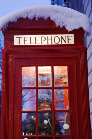 East asian female tourist in the red telephone booth  photo