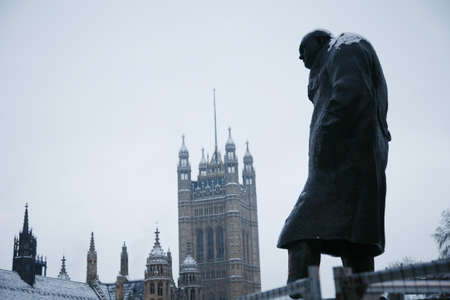 churchill: Churchill Statue in Parliament Square, London and Victoria Tower in the distance.