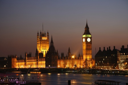 Westminster Palace, Big Ben and Victoria Tower, seen from Hungerford Bridge at Dusk Stock Photo