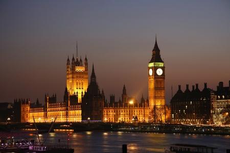 Westminster Palace, Big Ben en de Victoria Tower, gezien vanaf de Hungerford Bridge at Dusk