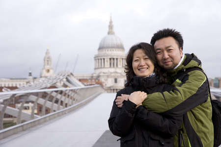 Smiling young East Asian couple at Millennium Bridge, St Paul Stock Photo - 12504649