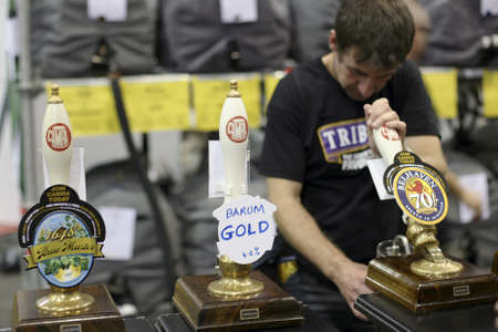 international beer: London, UK - August 04, 2010: Brewers of The Great British Beer Festival, 2010, at Earls Court, Britains biggest beer festival. Visitors can try wide range of real ales, ciders, perries and international beers.