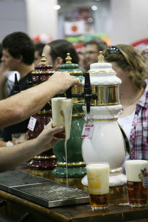 international beer: London, UK - August 05, 2010: Brewers of The Great British Beer Festival, 2010, at Earls Court, Britains biggest beer festival. Visitors can try wide range of real ales, ciders, perries and international beers.