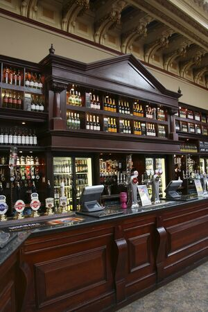 beer pump: Edinburgh, UK - July 24, 2010: Inside view of a public house, known as pub, for drinking and socializing, is the focal point of the community, Pub business, now about 53,500 pubs in the UK, has been declining every year.