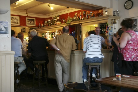 London, UK - July 31, 2010: Inside view of a public house, known as pub, for drinking and socializing, is the focal point of the community, Pub business, now about 53,500 pubs in the UK, has been declining every year.