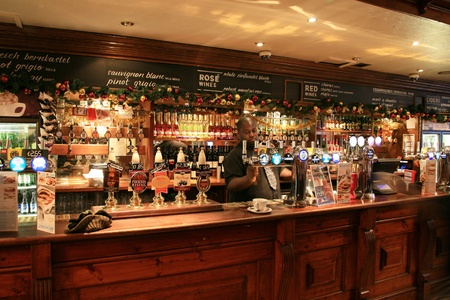 London, UK - December 01, 2010: Inside view of a public house, known as pub, for drinking and socializing, is the focal point of the community, Pub business, now about 53,500 pubs in the UK, has been declining every year.   Stock Photo - 12468968