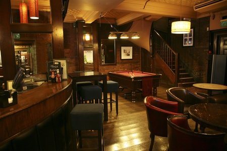 London, UK - August 30, 2010: Inside view of a public house, known as pub, for drinking and socializing, is the focal point of the community, Pub business, now about 53,500 pubs in the UK, has been declining every year.