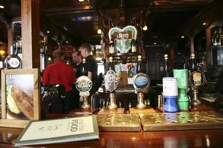 beer tap: London, UK - August 30, 2010: Inside view of a public house, known as pub, for drinking and socializing, is the focal point of the community, Pub business, now about 53,500 pubs in the UK, has been declining every year.    Editorial