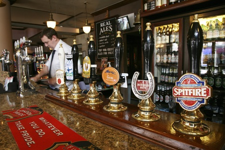 beer tap: London, UK - September 02, 2010: Inside view of a public house, known as pub, for drinking and socializing, is the focal point of the community, Pub business, now about 53,500 pubs in the UK, has been declining every year.   Editorial