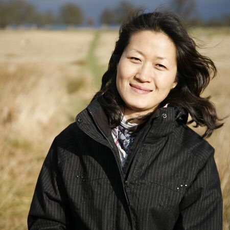 asian woman face: Portrait smiling asian woman looking at camera in the field    Stock Photo