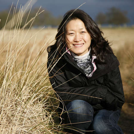 Portrait smiling asian woman looking at camera in the field photo
