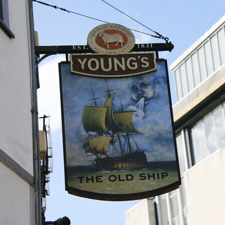 London, UK - July 15, 2010: English pub sign. Public house, known as pub, for drinking and socializing, is the focal point of the community. Pub business, now about 53,500 pubs in the UK, has been declining every year.