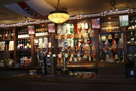 London, UK - April 12, 2006: Inside view of a public house, known as pub, for drinking and socializing, is the focal point of the community, Pub business, now about 53,500 pubs in the UK, has been declining every year.