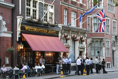 London, UK - June 7, 2006: Outside view of a public house, known as pub, for drinking and socializing, is the focal point of the community, Pub business, now about 53,500 pubs in the UK, has been declining every year.