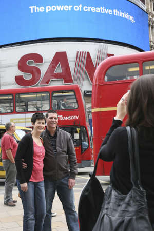 London, UK - August 12, 2010: Tourists in Piccadilly Circus, famous tourist attraction, road junction, built in 1819, meeting place, tourist attraction, in West End, inks to Shaftesbury Avenue, Regent Street, Haymarket, Leicester Square and Glasshouse Str