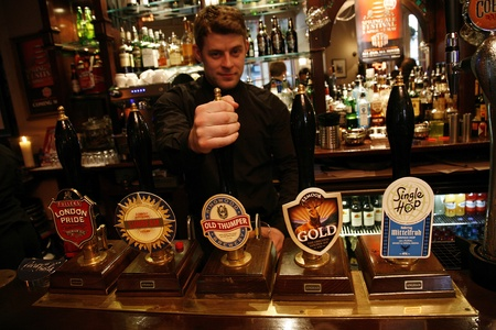 beer pump: London, UK - April 30, 2012: Inside view of a public house, known as pub, for drinking and socializing, is the focal point of the community, Pub business, now about 53,500 pubs in the UK, has been declining every year.   Editorial