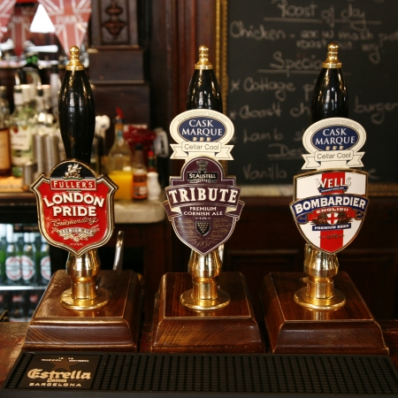 beer tap: London, UK - May 5, 2012: Inside view of a public house, known as pub, for drinking and socializing, is the focal point of the community, Pub business, now about 53,500 pubs in the UK, has been declining every year.