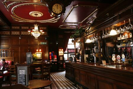 british foods: London, UK - May 5, 2012: Inside view of a public house, known as pub, for drinking and socializing, is the focal point of the community, Pub business, now about 53,500 pubs in the UK, has been declining every year.