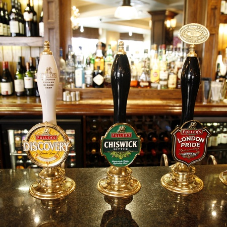 beer pump: London, UK - May 12, 2012: Inside view of a public house, known as pub, for drinking and socializing, is the focal point of the community, Pub business, now about 53,500 pubs in the UK, has been declining every year.  Editorial