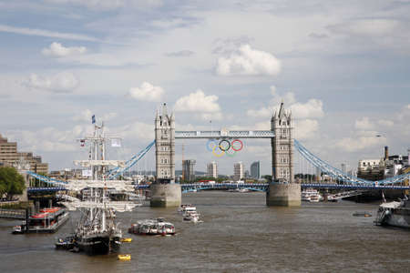 however: London, UK - July 30, 2012: 2012 London Olympic Rings on Tower Bridge. The rings were originally lowered into place on June 27th 2012, however, unveiled on 26th, to mark one month before the start of the London 2012 Olympic games.  Editorial