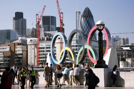 London, UK - July 26, 2012: Olympic rings being transported down the River Thames during the 2012 London Olympic Games, Gherkin and Tower 42 are in the distance.