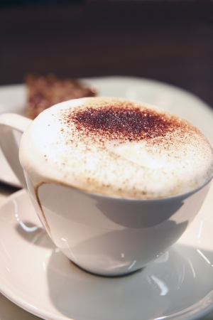 capuccino: Warm cup of coffee on brown background