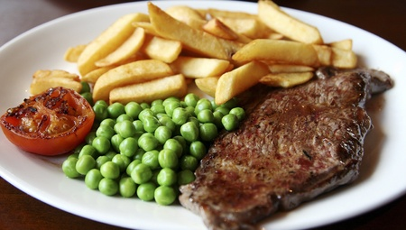 close-up of grilled beef steak served with chips, green peas and slice of tomato.