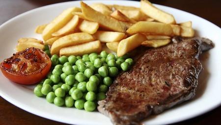 close-up van gegrilde biefstuk geserveerd met frites, groene erwten en plakje tomaat.