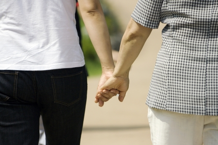 Old mother and young daughter holding hands walking in park  Stock Photo