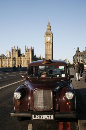 London, UK - October 27, 2012: London Taxi FX4, also called hackney carriage, black cab, Big Ben in the back ground. FX4 is manufactured by the London Taxis International, LTI.