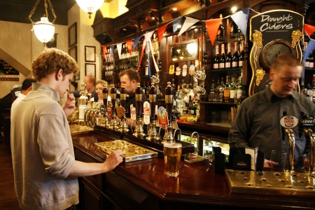 pub: London, UK - July 26, 2012: Inside view of a public house, known as pub, for drinking and socializing, is the focal point of the community, Pub business, now about 53,500 pubs in the UK, has been declining every year.