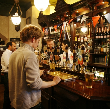 focal point: London, UK - July 26, 2012: Inside view of a public house, known as pub, for drinking and socializing, is the focal point of the community, Pub business, now about 53,500 pubs in the UK, has been declining every year.