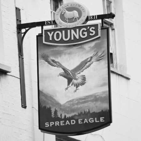 London, UK - June 17, 2012: English pub sign. Public house, known as pub, for drinking and socializing, is the focal point of the community. Pub business, now about 53,500 pubs in the UK, has been declining every year.