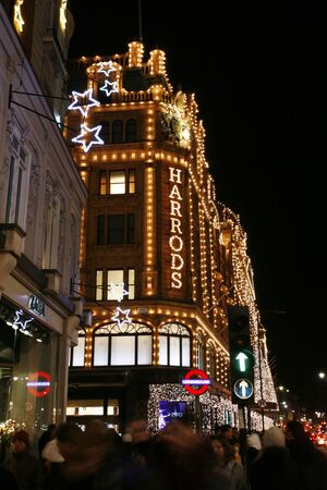harrods: London, UK - December 2, 2012: Christmas lights on Brompton Road, crowds present, Harrods in the distance. Harrods was opened at 1824 and now it is one of the most famous luxury store in London.