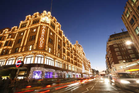 harrods: London, UK - December 8, 2012: Night View of Harrods, located in Brompton Road, with christmas decoration, crowds present. Harrods was opened at 1824 and now it is one of the most famous luxury store in London.