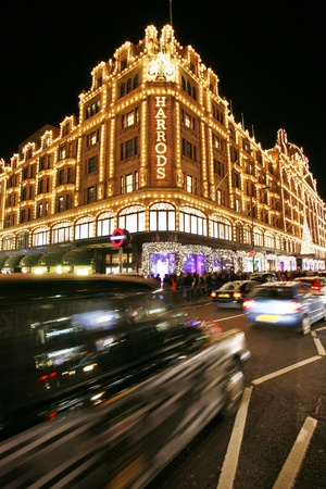 crowd tail: London, UK - December 8, 2012: Night View of Harrods, located in Brompton Road, with christmas decoration, crowds present. Harrods was opened at 1824 and now it is one of the most famous luxury store in London.