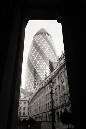 London , UK - March 25, 2012: Outside view of 30 St Mary Axe, also called Gherkin, a skyscraper in the City of London, 180 metres height, 41 floors, completed in 2003, seen from pedestrian walk path.