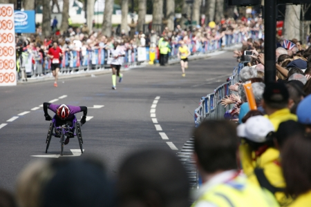 majors: London, UK - April 21, 2013: Wheelchair racing contestants in the crowds of London Marathon runners. The London Marathon is next to New York, Berlin, Chicago and Boston to the World Marathon Majors, the Champions League in the marathon.