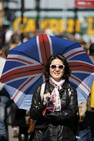 Smiling asian woman, in the middle of a crowd of Camden Street, with Union Jack umbrella photo