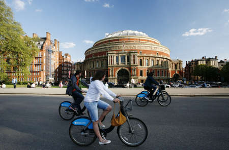 at ease: London, UK - May 26, 2013 : Tourists on rental bike passing by Royal Albert Hall. Londons bicycle sharing scheme, to help ease traffic congestion, sponsored by Barclays, was launched on 30 July 2010. Currently there are some 6,000 bikes and 400 docking s Editorial