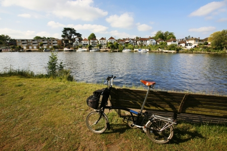 kingston: Folding bicycle stand, leaning against a riverside bench, near Thames River in Kingston upon Thames