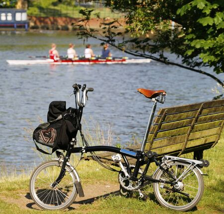 kingston: Folding bicycle stand, leaning against a riverside bench, boat and rowers present, near Thames River in Kingston upon Thames
