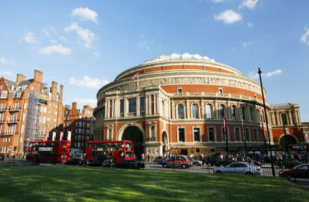 hackney carriage: London, UK - May 26, 2013 : Outside view of Royal Albert Hall with green field, people and cars present on the street and buses and taxis passing by. Royal Albert Hall is a concert hall, most famous for summer Proms concerts since 1941, Completed in 1871