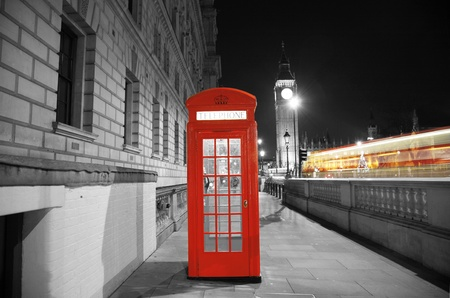 Red Telephone Booth at night, Big Ben in the distance. Red phone booth is one of the most famous London icons.